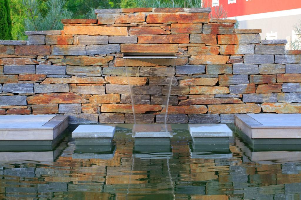 FREIRAUM Natursteinmauer mit Wasserspeier